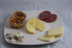 Clockwise from upper left: Mini Baklava, Chianti Salami, Cabot Sharp Cheddar, and Roquefort, with Honey Crisp Apple and Fire Blossom Honey in the middle.